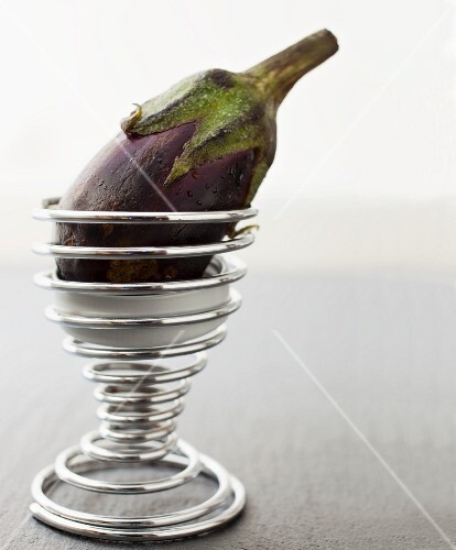 A baby aubergine in a spiral ice cream cone holder