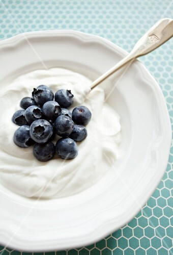 Vanilla yogurt with blueberries on a blue patterned surface