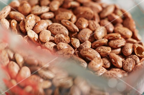 Dried organic pinto beans in a measuring jug (close-up)
