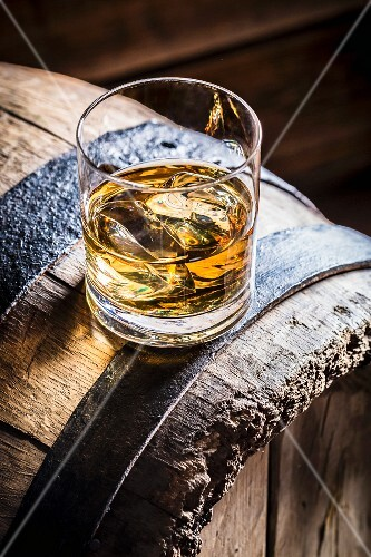 A glass of whiskey with ice on an old wooden barrel