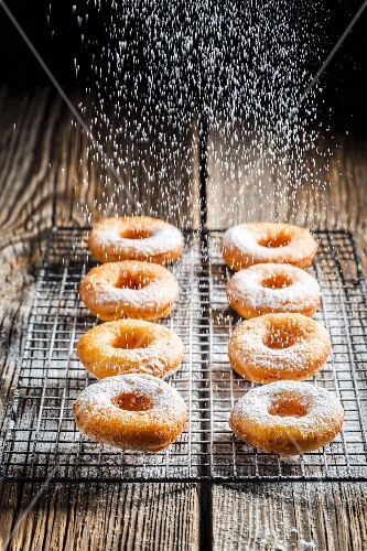 Freshly baked doughnuts being dusted with icing sugar