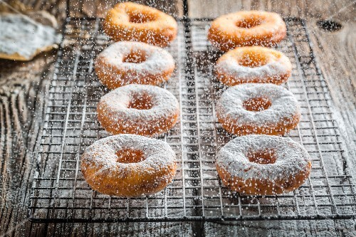 Freshly baked doughnuts dusted with icing sugar
