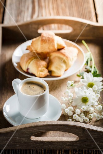 Espresso, croissants and flowers on a wooden tray