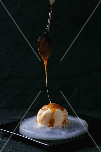 Caramel and hazelnut butter ice cream with pouring caramel on a plate of ice