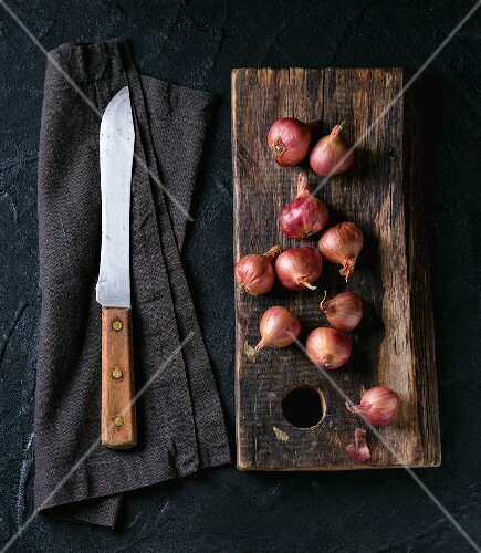 Small red onions on a wooden board and an old knife on a fabric napkin