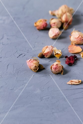 Dry rosebuds and chamomile flowers on grey textured surface