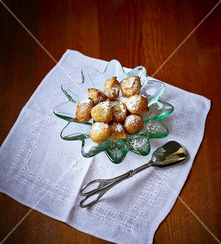 Doughnuts with icing sugar and pastry tongs