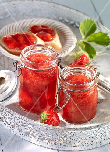 Strawberry jam in jars and on bread