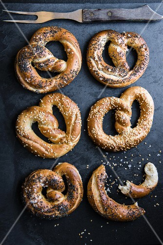 Pretzels on a dark stone surface (seen from above)