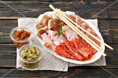 An Italian meat platter (mortadella, salami, ham with grissini and pesto)