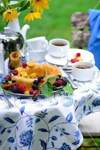 Rum baba with fresh fruit on summery outdoor table
