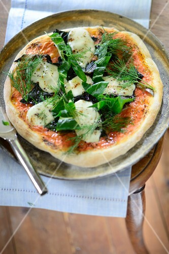 Pizza with braised green vegetables, mozzarella, tomatoes and dill oil