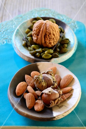 Pistachio nuts, walnuts, almonds and hazelnuts in ceramic bowls