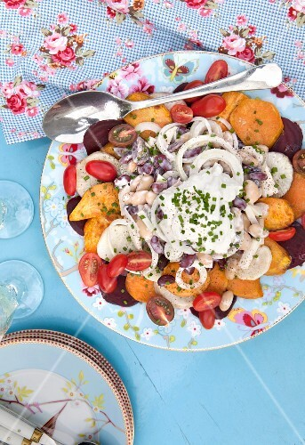 Warm salad with beetroot, sweet potatoes, cherry tomatoes and beans with yoghurt dressing