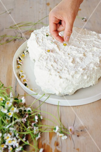 A heart-shaped creamy carrot cake being decorated with daisies