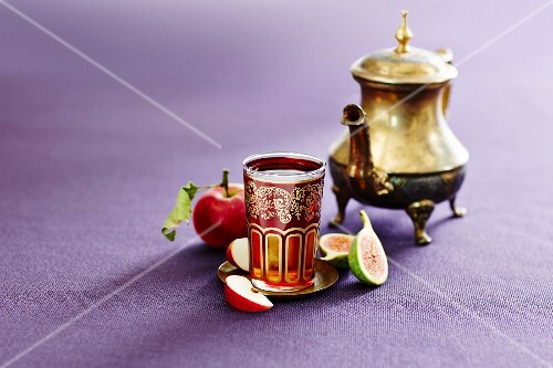 A silver teapot and a glass of Turkish apple tea