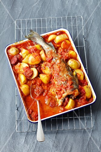 Oven-baked cod with potatoes, chorizo and tomato sauce