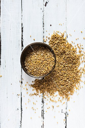 Coarsely crushed freekeh in a bowl and on a wooden surface