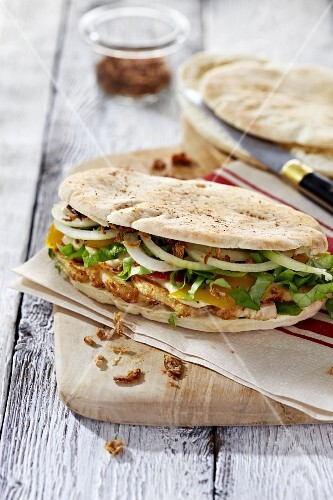 Unleavened bread with hummus, chicken, onion rings and salad