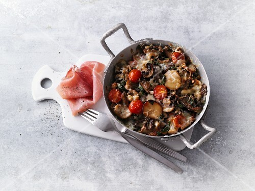Fried gratinated mushrooms with tomatoes and smoked ham
