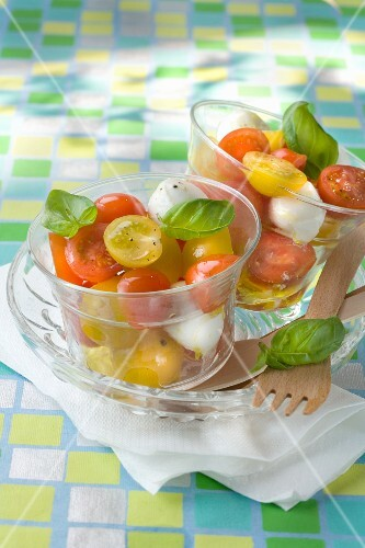 Cherry tomatoes with mozzarella and basil in glasses