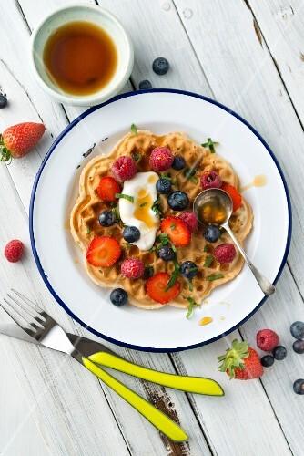 A vegan, gluten-free waffle with fresh berries, yoghurt and honey