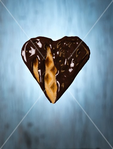 A heart-shaped vegan waffle dipped in chocolate