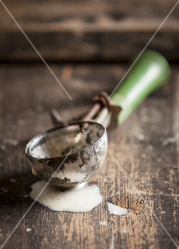 An old ice cream scoop with a green handle in a pool of melted vanilla ice cream on a wooden surface