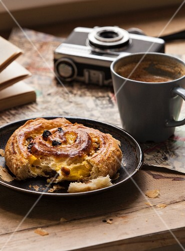 A cinnamon bun with raisins, a cup of coffee, a camera and a map on the wooden table
