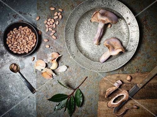 An arrangement of mushrooms, bay leaves, garlic and borlotti beans