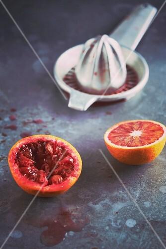 A halved blood orange with a juicer