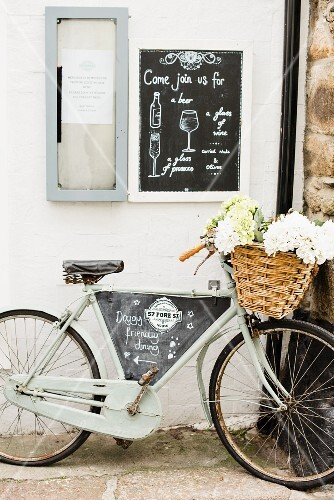 A bicycle with a basket full of flowers and advertising sign for restaurant