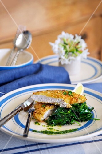 Breaded chicken escalope with spinach and lemons