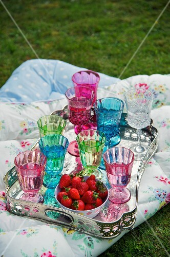 Silver platter with colorful glasses and strawberries