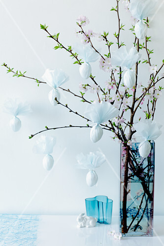 Easter eggs wrapped in napkins hanging from a cherry blossom sprig