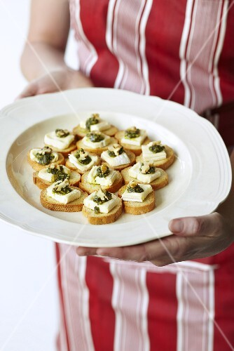 A woman serving cheese and pesto canapés