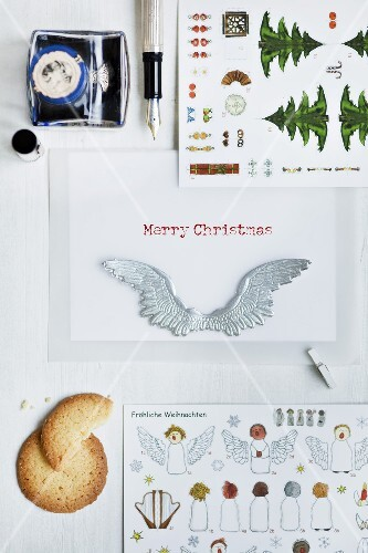 Verschiedene Weihnachtskarten, Schreibfeder und ein Plätzchen