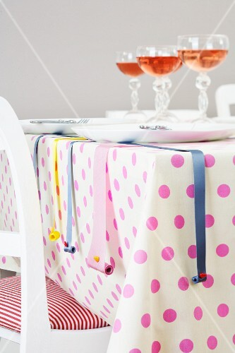 A table laid with a spotted tablecloth and decorative ribbons