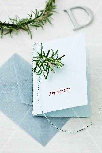 Dinnerkarte dekoriert mit Rosmarinzweigen