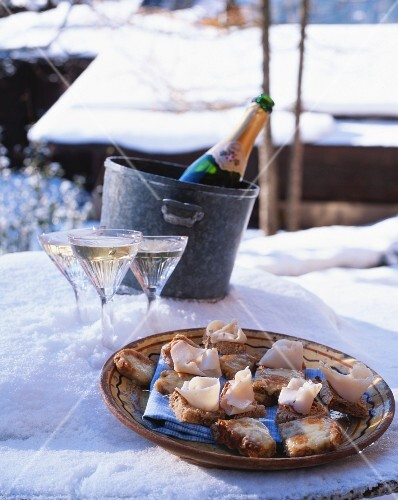 Champagne and a plate of ham canapés in the snow (Chamonix, France)