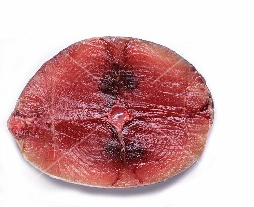 A raw tuna steak on a white surface