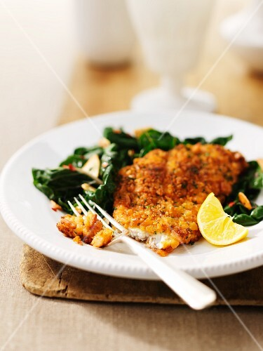 A breaded fish fillet with spinach