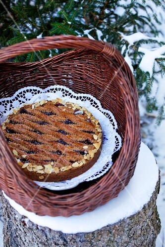 A Linz tart in a basket on a tree stump in the winter