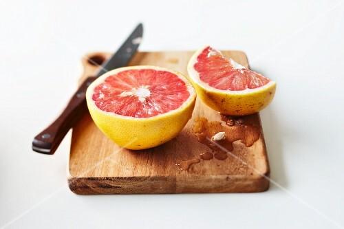 Cut pink grapefruit on chopping board