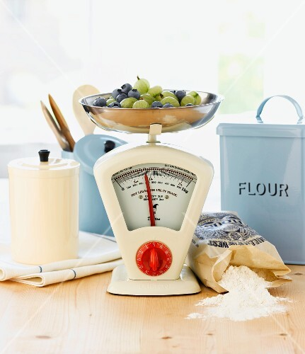 Berries on kitchen scales, baking ingredients and wooden spoons
