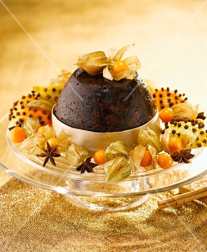 Christmas pudding with cape gooseberries on gold cloth