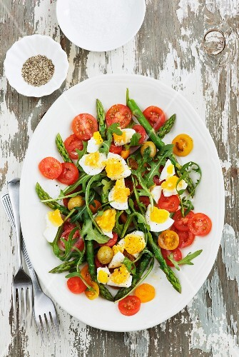 Summer salad with steamed asparagus, rocket, cherry tomatoes, olives and egg