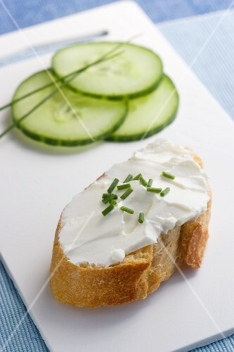 Sliced cucumbers and a baguette topped with cream cheese and chives
