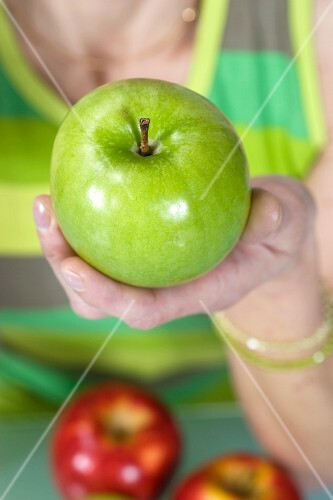 A woman holding a green apple
