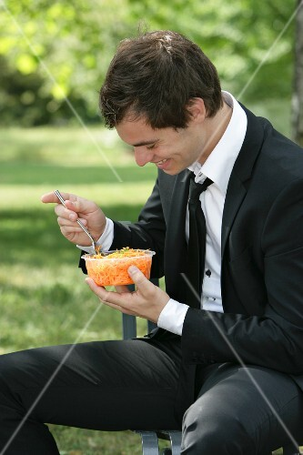 A man eating grated carrots on a park bench